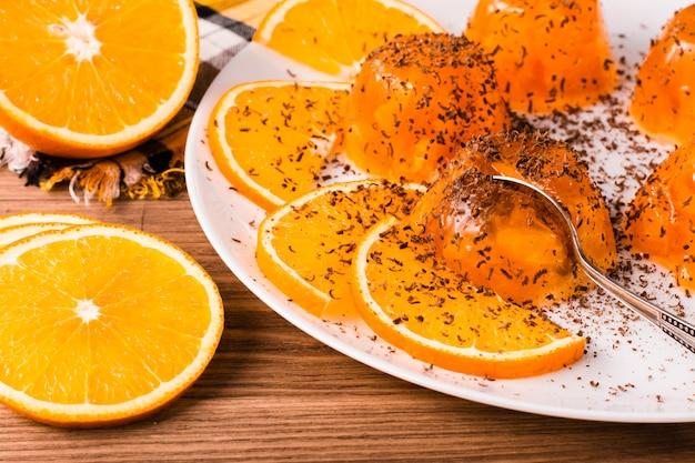 Orangengelee mit schokoladenstückchen, einem löffel und orangenscheiben