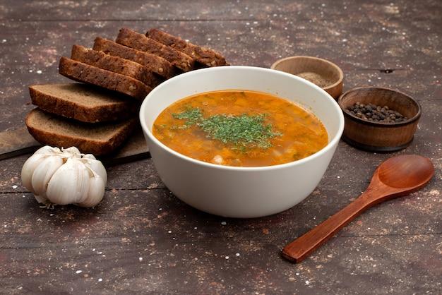 Orangengemüsesuppe der vorderansicht mit brotlaib und knoblauch auf brauner nahrungsmittelsuppe