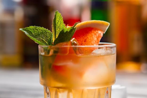 Orangengetränk in einem glas. eis und minzeblätter. köstlicher hausgemachter cocktail mit grapefruit. einfaches rezept für ein sommergetränk.