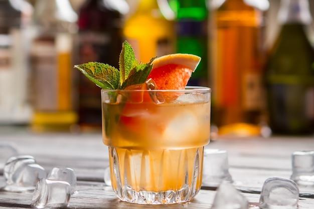 Orangengetränk mit eis. grapefruitscheibe im getränk. leckerer sommercocktail. saft und importierter alkohol.