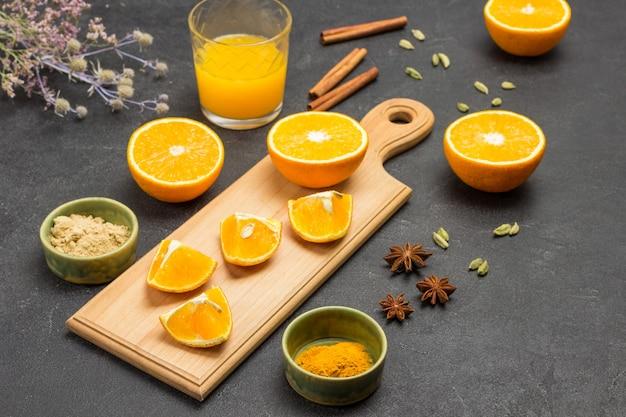 Orangenhälften auf schneidebrett. sternanis, zimtstangen und kardamom auf dem tisch. kurkuma und ingwer in grüner schüssel. ein glas saft. schwarzer hintergrund. ansicht von oben.