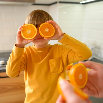 Orangenhälften bedecken die augen