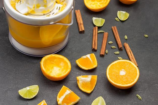 Orangenhälften und gewürze auf dem tisch. entsafter mit fertigem saft. schwarzer hintergrund. ansicht von oben