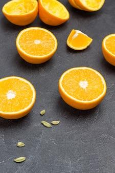 Orangenhälften und kardamom auf dem tisch. platz kopieren. schwarzer hintergrund. ansicht von oben.