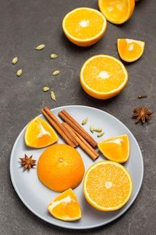 Orangenhälften und zimtstangen auf grauer platte. sternanis und gehackte orangen auf dem tisch. schwarzer hintergrund. ansicht von oben