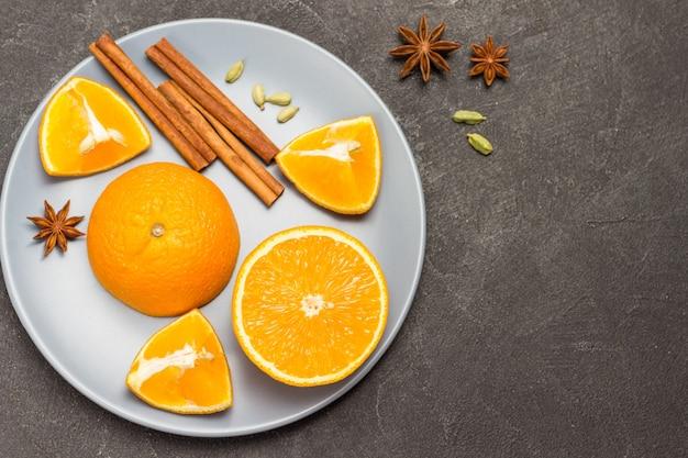 Orangenhälften, zimtstangen und sternanis auf grauem teller. gewürze auf dem tisch. schwarzer hintergrund. platz kopieren. flach legen