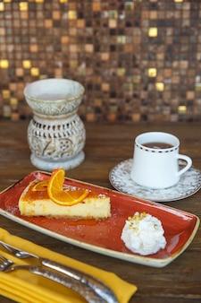 Orangenkäsekuchen mit sahne, serviert mit tee