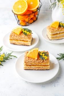 Orangenkuchen dekoriert mit frischen orangenscheiben und mimosenblüten auf licht