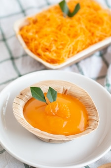 Orangenkuchen mit orangensauce-belag in der nutural-schale, außer erde-paket