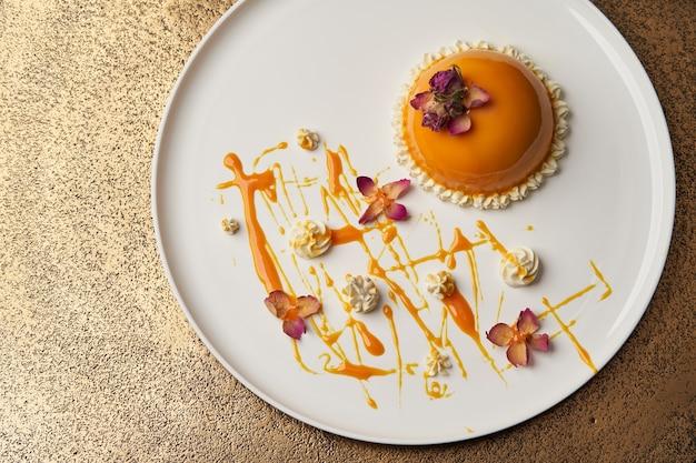 Orangenkuchen mit sahne auf weißem teller. bananen-mousse-kuchen, luxus-restaurant-dessert