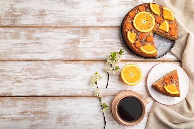 Orangenkuchen und eine tasse kaffee auf einem weißen holz