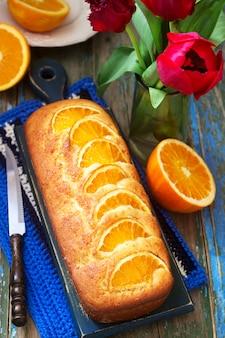 Orangenkuchen, verziert mit orangenscheiben auf einem hintergrund von saftigen orangen und einem strauß tulpen. rustikaler stil.