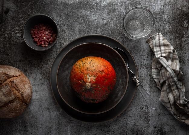 Orangenkürbis auf einem dunkelgrauen teller mit schinken und brot
