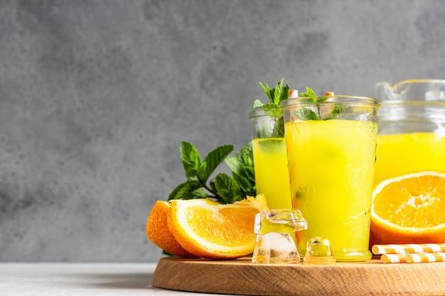 Orangenlimonade im glas mit frischer orange und minze über hellgrauer steintabelle. erfrischendes sommergetränk.