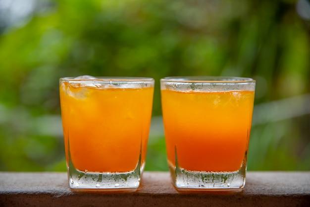 Orangensaft auf 2 blättern auf einem natürlichen hintergrund.