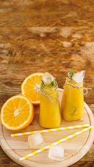 Orangensaft auf einem holztablett. geschnittene orange und eiswürfel. snack im resort, kühle an einem heißen sommertag. vertikales foto