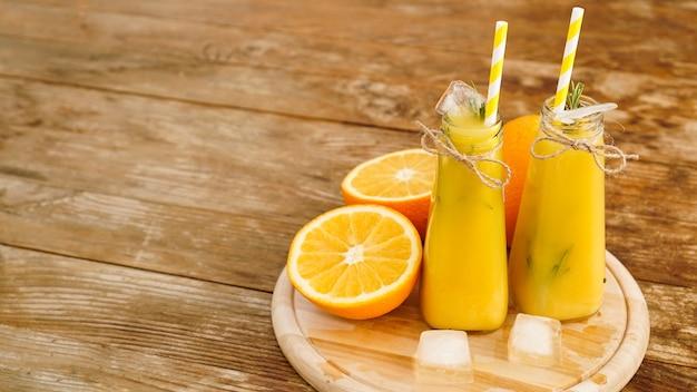 Orangensaft auf einem holztablett. geschnittene orange und eiswürfel. snack im resort, kühle an einem heißen sommertag.