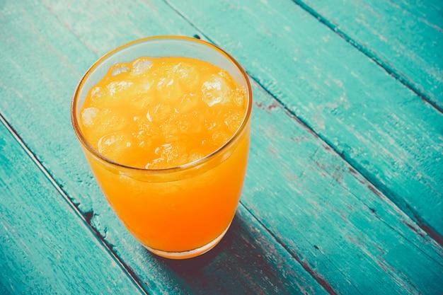 Orangensaft der draufsicht im glas mit eis auf hölzernem sommerzeitkonzept des ozeanblaus.