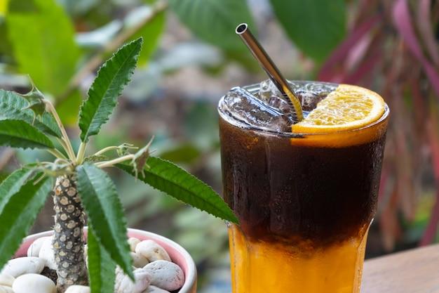 Orangensaft-eiskaffee in glas mit orangenfrüchten und pflanzen