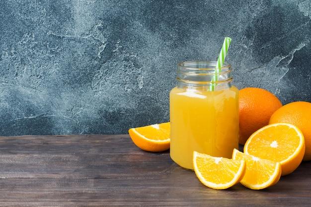 Orangensaft im glasgefäß und in den orangen der frischen früchte auf dunklem hintergrund mit kopienraum.