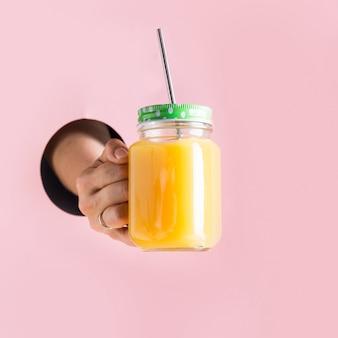 Orangensaft im weckglas, das weibliche hand durch im loch hält.