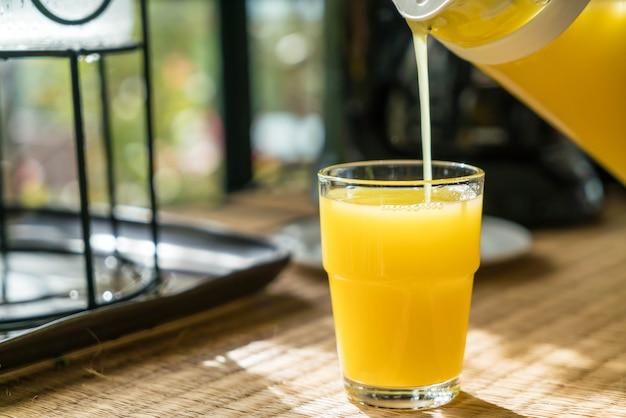 Orangensaft in ein glas gießen