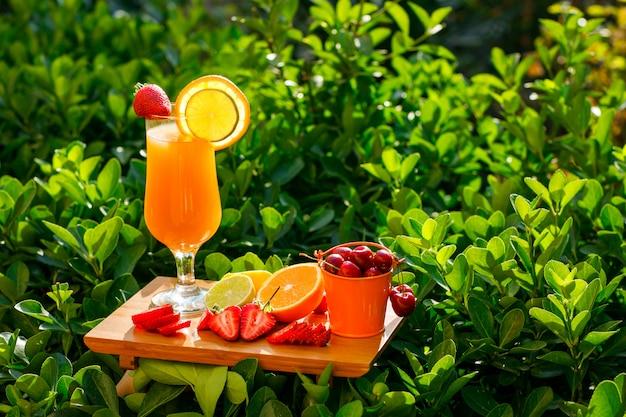 Orangensaft in einem becher mit zitrusfrüchten, erdbeere, kirsche, schneidebrett seitenansicht auf einer wiese
