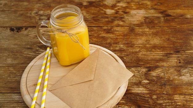 Orangensaft in einem glas auf hölzernem hintergrund. umschlag mit einem brief auf einem holzbrett. morgennotiz und obstfrühstück
