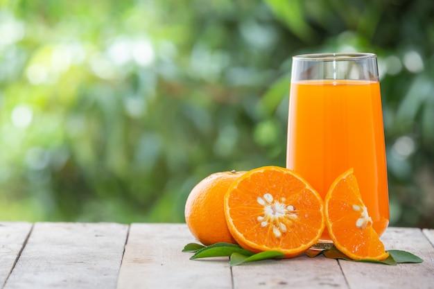 Orangensaft in einem glas mit orangen