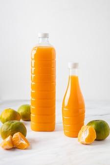 Orangensaft in einer flasche auf marmor mit orangen