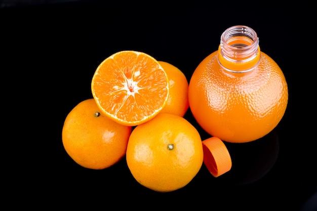 Orangensaft in einer flasche und orange auf schwarzem hintergrund