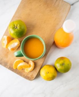 Orangensaft in einer tasse und in einer flasche auf marmor