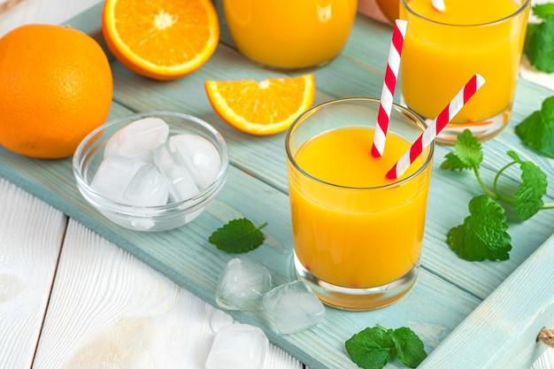 Orangensaft in gläsern mit tuben auf einem schreibtisch aus minze und orangen. horizontale ansicht