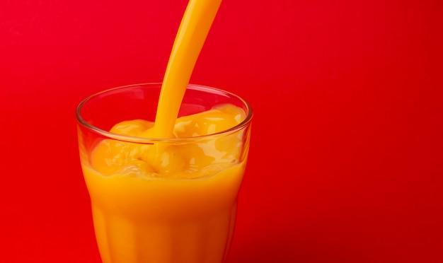 Orangensaft in glas gießen