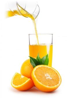 Orangensaft in glas und orangen gießen