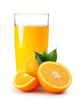 Orangensaft in glas und orangen mit blättern gießen