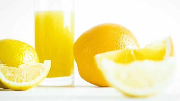Orangensaft in glas- und orangenscheiben auf weißem holztisch