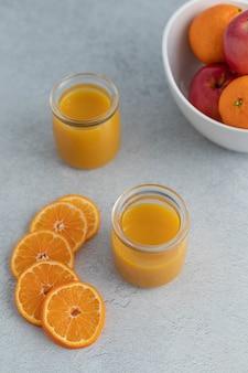 Orangensaft in klarem glas nahe geschnittenen orangen und orangen- und apfelfrüchten in runder schüssel