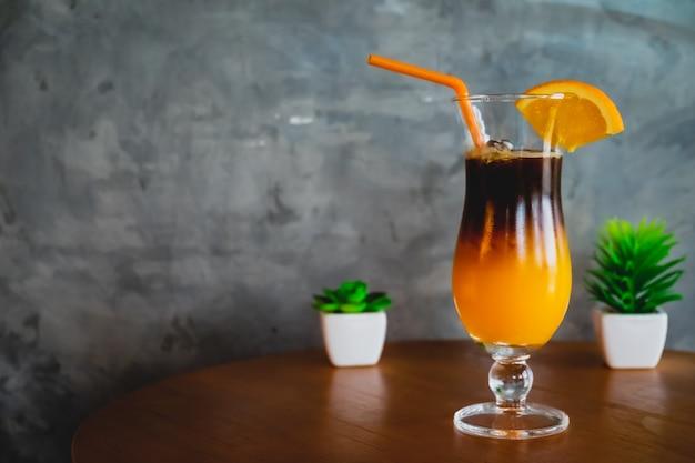 Orangensaft mit dem espresso geschossen auf holztisch