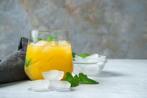 Orangensaft mit eis und minze auf einem grauen schreibtisch. seitenansicht, nahaufnahme, mit platz zum kopieren.