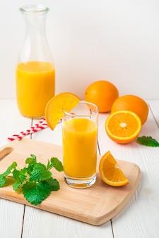 Orangensaft mit glas und minze erscheint nicht auf einem hellen schreibtisch mit dekanter. seitenansicht, vertikal.