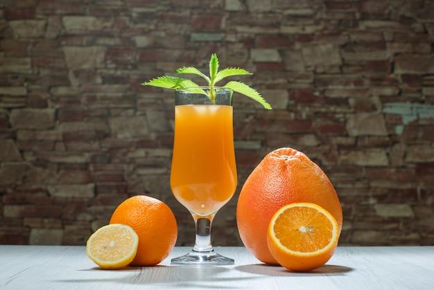 Orangensaft mit minze, zitrusfrüchten in einem becher auf holz- und ziegelsteinhintergrund, seitenansicht.