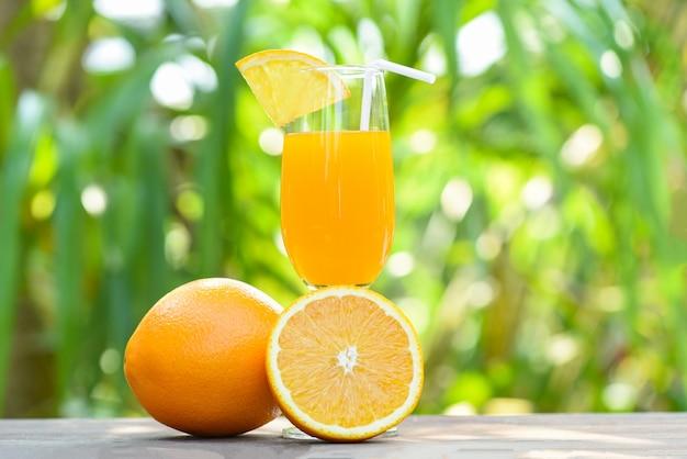 Orangensaft mit orange frucht des stückes auf glas mit naturgrün-sommerhintergrund