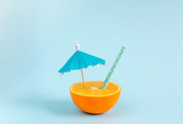 Orangensaft mit stroh und regenschirm. orange beinahe eingeschnitten auf blauen pastellhintergrund. minimaler sommer