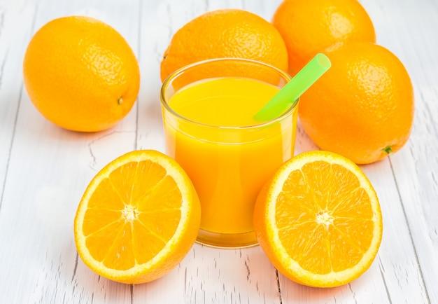 Orangensaft und orangen auf holztisch