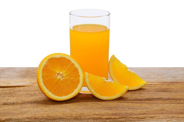 Orangensaft und orangenscheiben auf einem holztisch.
