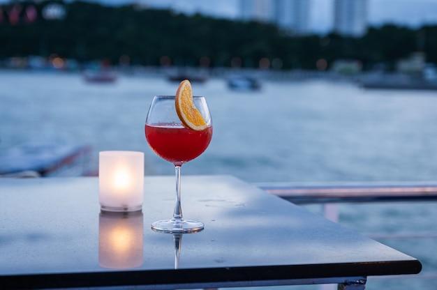 Orangensaftcocktail im weinglas und in der lampe auf tisch am meer