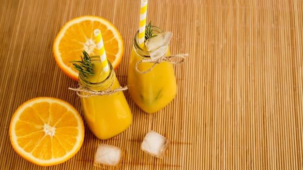Orangensaftflaschen und papierstrohhalme. eisiges getränk an einem sonnigen tag. eisstücke in einer flasche und auf einer bambusserviette