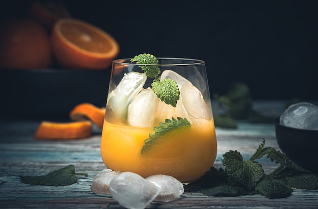 Orangensaftgetränk mit eis und minze auf einem dunklen schreibtisch. seitenansicht, nahaufnahme.