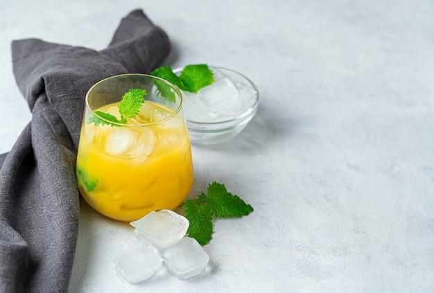Orangensaftgetränk mit eis und minze auf einem grauen schreibtisch. seitenansicht mit kopierraum.